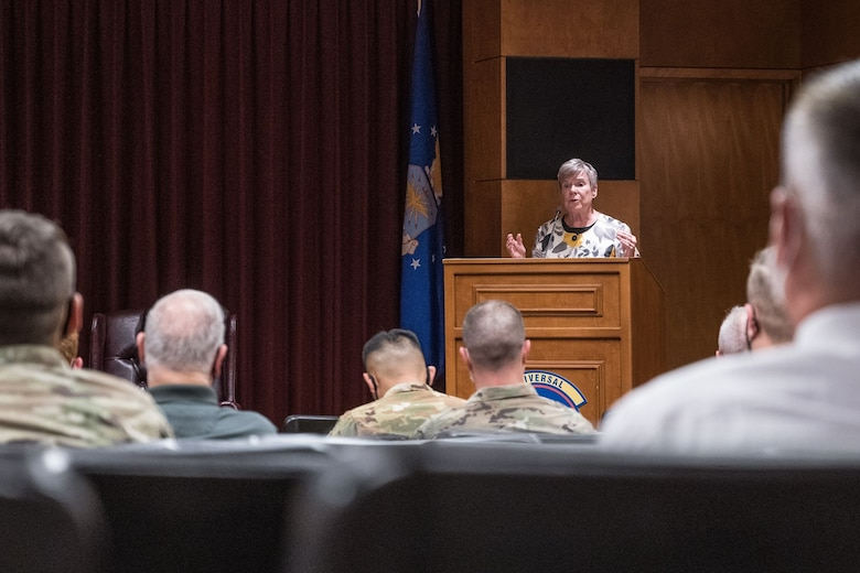 A woman stands at a podium in front of a crowd of uniformed service members in a conference room