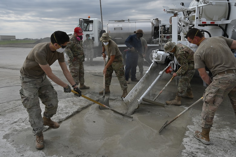 Four military members smooth quick-set concrete with rakes in a square hole in an effort to patch the hole for training at the North Dakota Air National Guard Regional Training Site, Fargo, N.D., Sept. 30, 2021. The concrete patching material is coming down a metal shoot from a machine called a volumetric mixer.