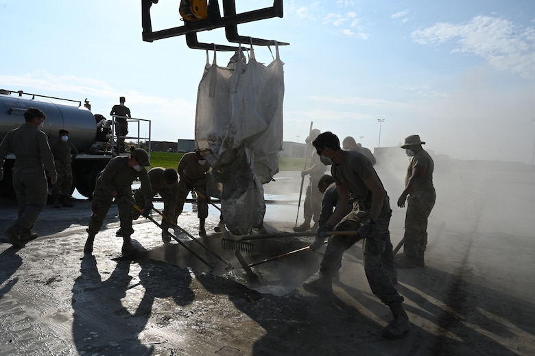 Eight military members rake liquid concrete material in a square hope on a concrete training runway at the North Dakota Air National Guard Base Regional Training Site, Fargo, N.D., Sept. 30, 2021.