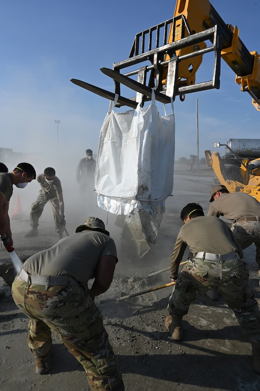 Five military members rake liquid concrete repair material as they smooth it into a square concrete hole in a concrete training runway at the North Dakota Air National Guard Regional Training Site, Fargo, N.D., Sept. 30, 2021.