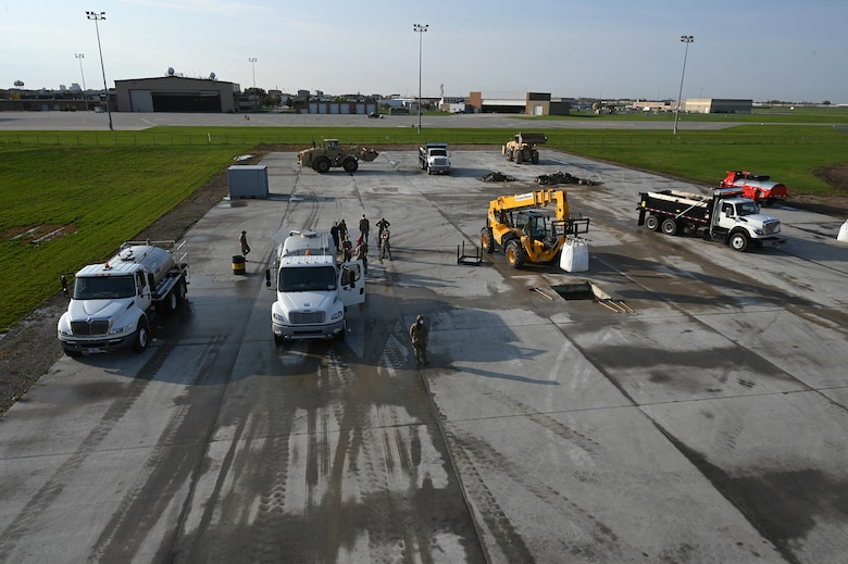 Heavy equipment and military person can be seen from an elevated view as they repair square holes in a concrete training runway at the North Dakota Air National Guard Regional Training Site, Fargo, N.D., Sept. 30, 2021.
