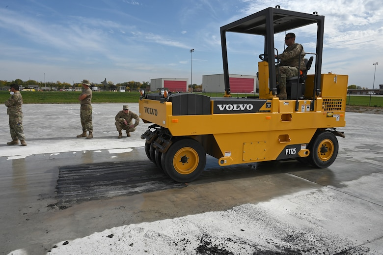 A military member operates a wheeled asphalt compactor as he levels an asphalt patch on a concrete training runway at the North Dakota Air National Guard Regional Training Site, Fargo, N.D., Sept. 29, 2021.