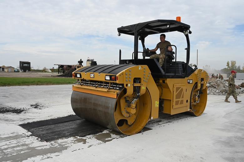 A military member operates an asphalt compactor as he levels an asphalt patch on a concrete training runway at the North Dakota Air National Guard Regional Training Site, Fargo, N.D., Sept, 29, 2021.