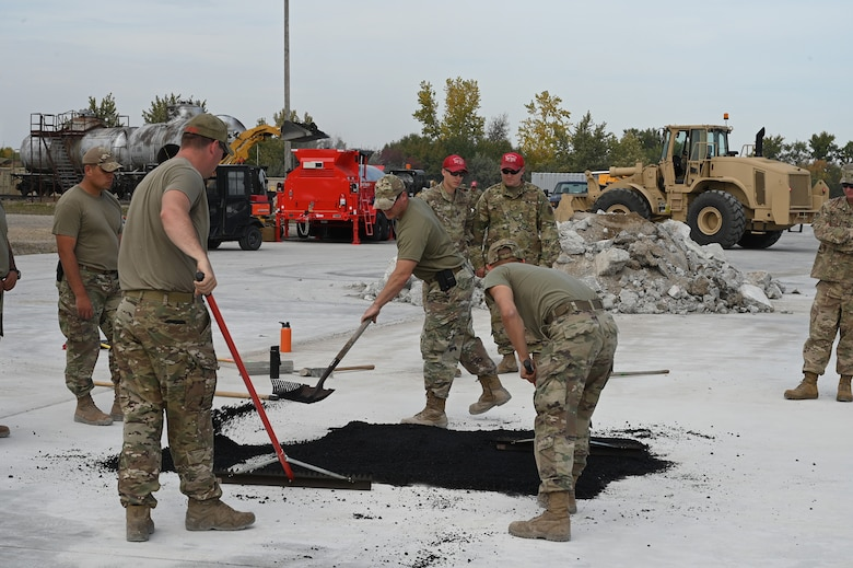 Three military members use rakes to smooth out asphalt material used to patch a square hole on a concreate training runway as several other personnel watch at the North Dakota Air National Guard Regional Training Site, Fargo, N.D., Sept. 29, 2021.