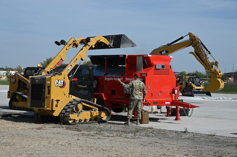 A military member directs a skid steer operator as he loads asphalt material into a large machine called an asphalt recycler to be reformed into patching material used to patch holes on a large concrete training runway at the North Dakota Air National Guard Regional Training Site, Fargo, N.D., Sept. 29, 2021.