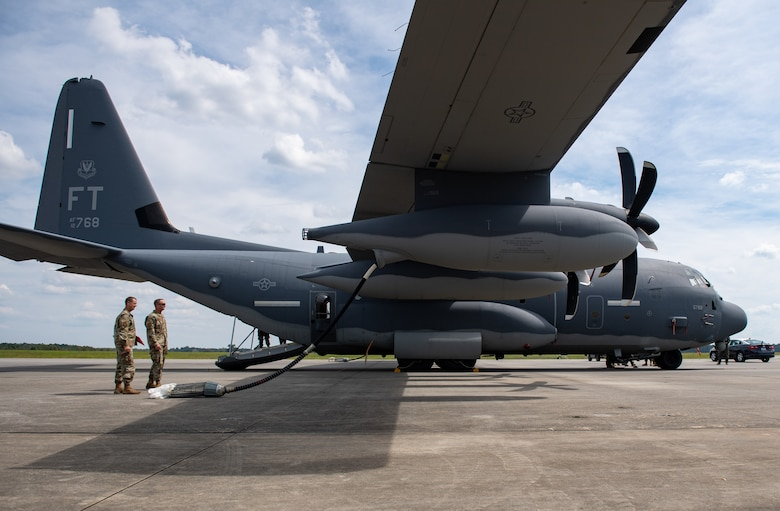 A photo of Airmen standing by an aircraft.
