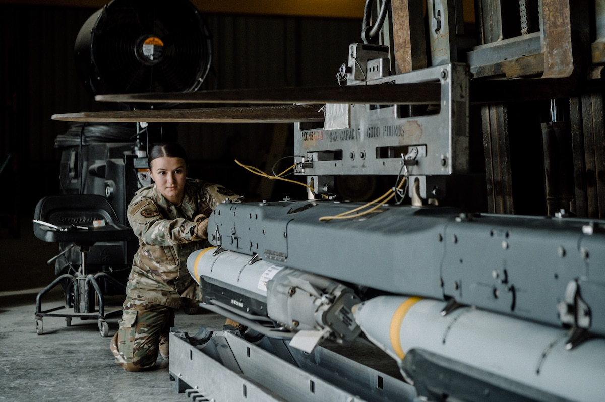 U.S. Air Force Senior Airman Angelica Range, munitions systems technician with the 379th Expeditionary Maintenance Squadron, guides a bomb rack unit equipped with four GBU-39 small diameter bombs into position at the munitions storage area on Al Udeid Air Base, Nov. 27, 2020. Many munitions Airmen at Al Udeid AB hail from Air Mobility Command bases where their primary function is to support cargo aircraft with countermeasures. At Al Udeid AB, they have the opportunity to qualify on the wide variety of weapons systems present in the U.S. Central Command area of responsibility.