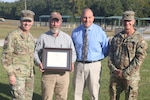 Todd Phillips, Maneuver Training Center Fort Pickett deputy chief of Plans, Training and Security, receives the Virginia Governor's Honor Award for Creative Customer Service Sept. 28, 2021, at Fort Pickett, Virginia. Maj. Gen. Timothy P. Williams, the Adjutant General of Virginia, retired Brig. Gen. Walt Mercer, Virginia Department of Military Affairs chief operations officer, and Lt. Col. James C. Shaver, Jr., MTC chief of Plans, Training and Security, presented the award to Phillips in front of his fellow MTC employees and thanked him for his service.