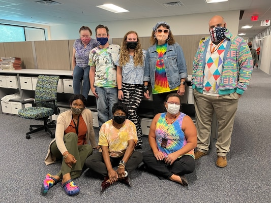 """Member of the U.S. Army Corps of Engineers Contracting team show off their Tie Dye during Contracting's """"Spirit Week,"""" a morale boosting event held in the lead up to a new fiscal year.  The weeks leading up to the end of a fiscal year can be extremely busy for Contracting, Resource Management and others who deal with an organization's finances."""