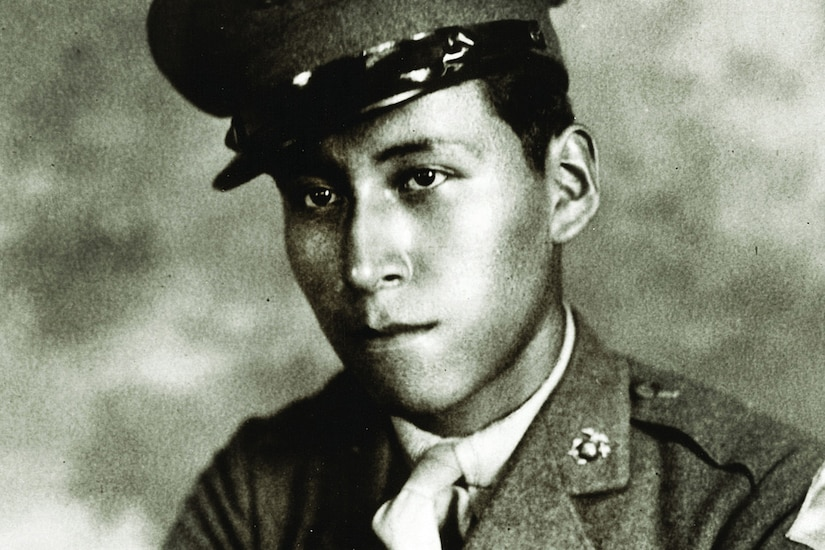A soldier wearing a cap poses for a photo.