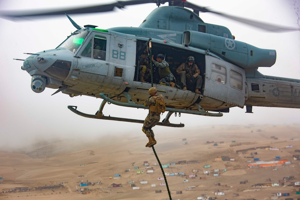A Marine fast-ropes from an airborne helicopter.