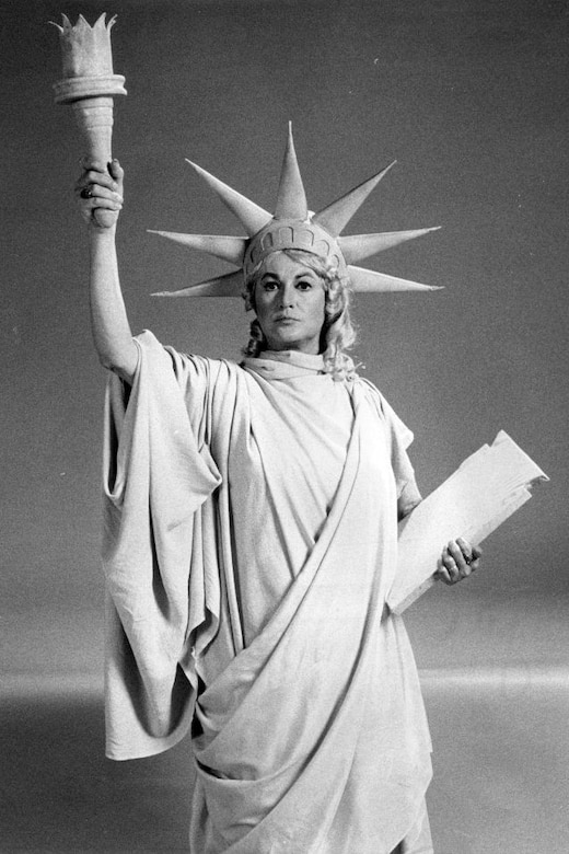A woman poses as the Statue of Liberty.