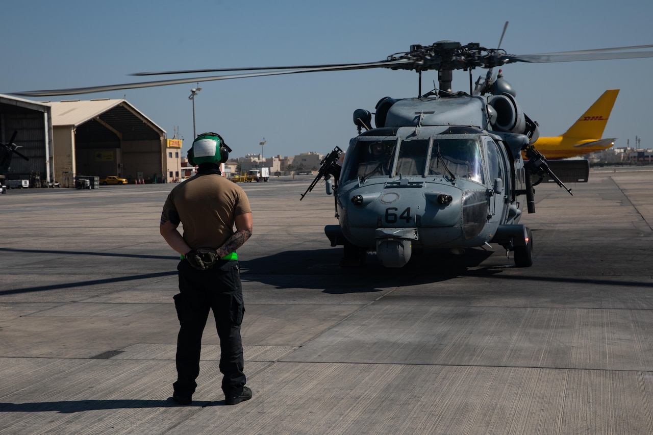 A soldier stands in front of a helicopter.