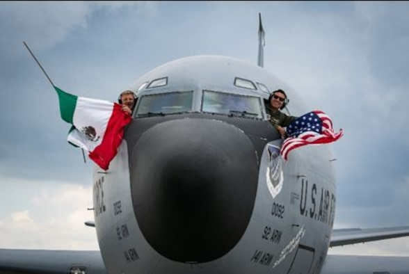 """Aircrew from the 92nd Air Refueling Wing, Fairchild Air Force Base, WA, wave the U.S. and Mexican flags during the Feria Aeroespacial México (FAMEX), or the Mexico Aerospace Fair at Base Aérea No.1 de Santa Lucía, Mexico, Sep. 25, 2021. The U.S. participated in the air show as the """"country of honor,"""" a special designation signifying the partnership and cooperation between both countries. (U.S. Air Force photo by 2nd Lt. Danny Rangel)"""