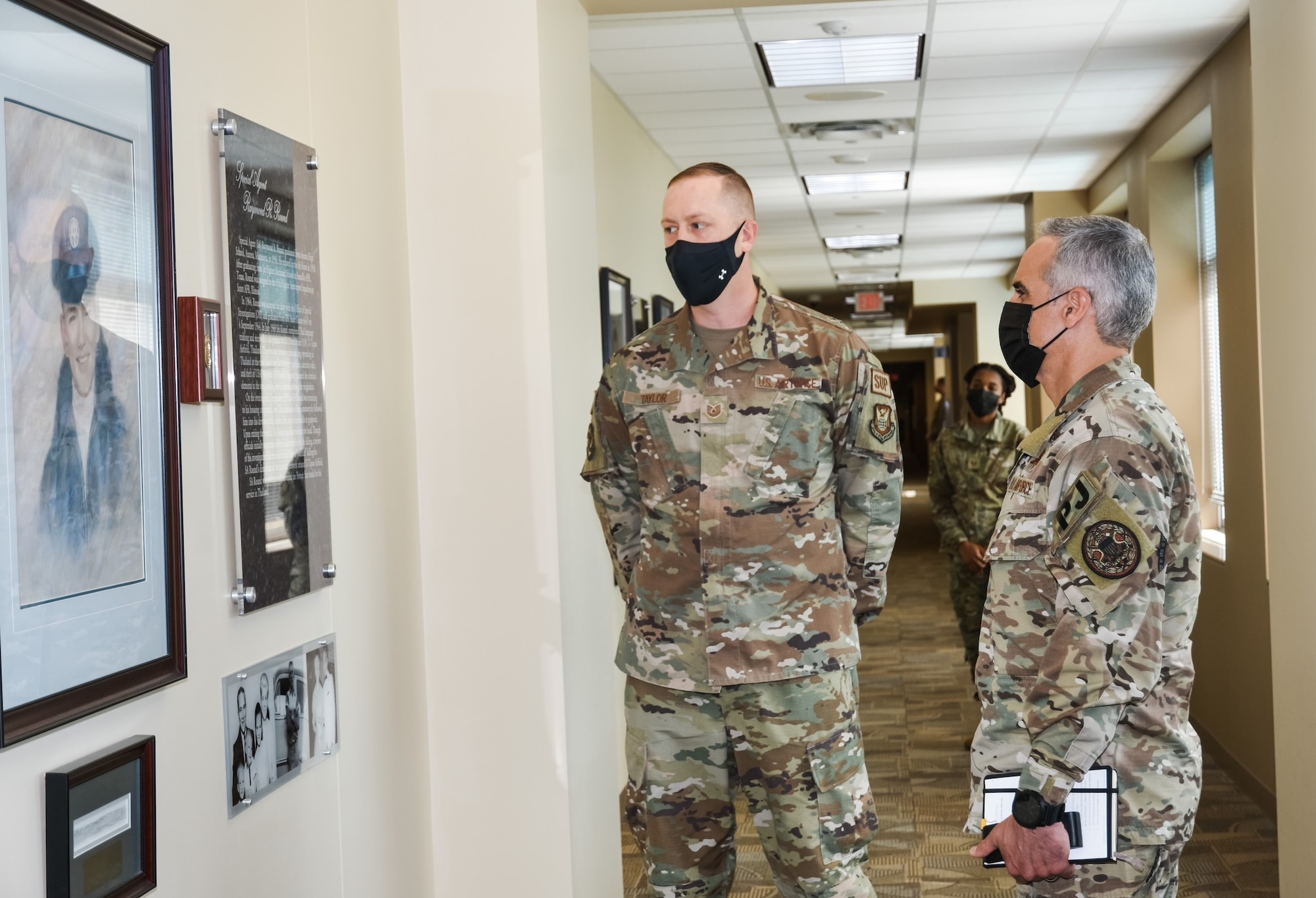 Tech. Sgt. William Taylor briefs the legacy of Office of Special Investigations Fallen Special Agent Raymond Round in the OSI Hall of Heroes, to SEAC Ramon Colon-Lopez, the Senior Enlisted Advisor to the Chairman of the Joint Chiefs of Staff, during his visit to OSI headquarters at Quantico, Va., Oct. 1, 2021. The SEAC visit supported OSI's observance of National Hispanic Heritage Month and this year's theme, Esperanza: A Celebration of Hispanic Heritage and Hope. (Photo by SA Christina Williams)