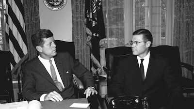 Two men sit talking in the White House Cabinet Room.