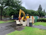 A heavy equipment operator uses pincers to smash filing cabinets in a staging yard.