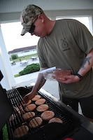 U.S. Air Force Tech. Sgt. Michael Daehnert, 81st Security Forces Squadron combat arms NCO in charge, grills burgers and hot dogs for Keesler families during the 81st SFS National Night Out at the Bay Ridge Community Center at Keesler Air Force Base, Mississippi, Oct. 5, 2021. The event, which was held to enhance the relationship between neighbors and law enforcement, included a military working dog demonstration, scavenger hunt and train rides. (U.S. Air Force photo by Kemberly Groue)