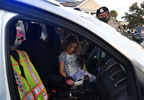 U.S. Air Force Airman Tyler Berry and Airman 1st Class Kaleb Brisbone, 81st Security Forces Squadron patrolmen, provide a patrol car tour to Madalynn Serabian, daughter of Maj. Christi Serabian, 81st Operational Medical Readiness Squadron mental health officer in charge, during the 81st SFS National Night Out at the Bay Ridge Community Center at Keesler Air Force Base, Mississippi, Oct. 5, 2021. The event, which was held to enhance the relationship between neighbors and law enforcement, also included a military working dog demonstration, scavenger hunt and train rides. (U.S. Air Force photo by Kemberly Groue)