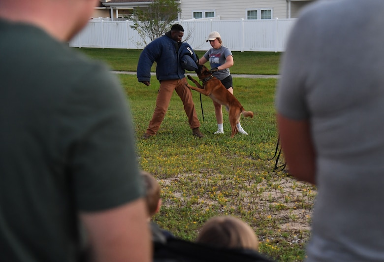 U.S. Air Force Senior Airman Ryan Wood and Staff Sgt. Victor Henderson, 81st Security Forces Squadron military working dog handlers, and Victor, 81st SFS military working dog, participate in a demonstration during the 81st SFS National Night Out at the Bay Ridge Community Center at Keesler Air Force Base, Mississippi, Oct. 5, 2021. The event, which was held to enhance the relationship between neighbors and law enforcement, included a military working dog demonstration, scavenger hunt and train rides. (U.S. Air Force photo by Kemberly Groue)