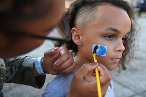 U.S. Air Force Senior Airman Aadriana Parker, 81st Security Forces Squadron patrolman, paints a design on the face of Nivon Brown, son of Capt. Alan Brown, 334th Training Squadron instructor, during the 81st SFS National Night Out at the Bay Ridge Community Center on Keesler Air Force Base, Mississippi, Oct. 5, 2021. The event, which was held to enhance the relationship between neighbors and law enforcement, included a military working dog demonstration, scavenger hunt and train rides. (U.S. Air Force photo by Kemberly Groue)