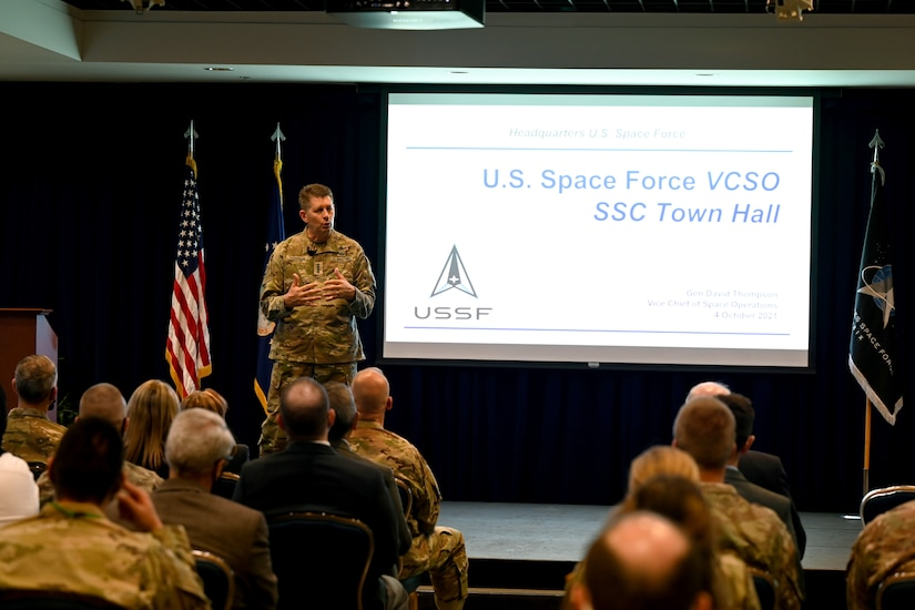 A military officer speaks to an audience from a stage.