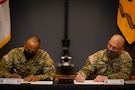 two men in army uniforms signing a memorandum on a table.