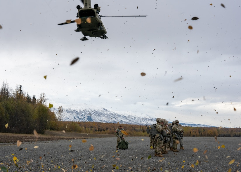 U.S. Army paratroopers assigned to the 4th Infantry Brigade Combat Team (Airborne), 25th Infantry Division, U.S. Army Alaska, brace against the rotor wash while waiting for a CH-47 Chinook.