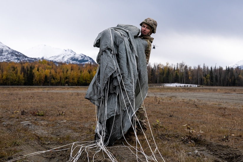 U.S. Army Spc. Chris Pulsipher, a paratrooper assigned to the 1st Squadron (Airborne), 40th Cavalry Regiment, 4th Infantry Brigade Combat Team (Airborne), 25th Infantry Division, U.S. Army Alaska, recovers his parachute after jumping from a CH-47 Chinook.
