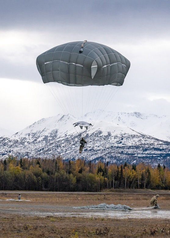 U.S. Army paratroopers assigned to the 4th Infantry Brigade Combat Team (Airborne), 25th Infantry Division, U.S. Army Alaska, land after jumping from a CH-47 Chinook.