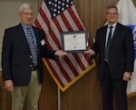Two men in business suits hold a framed award between the two of them while standing in front of an American flag.