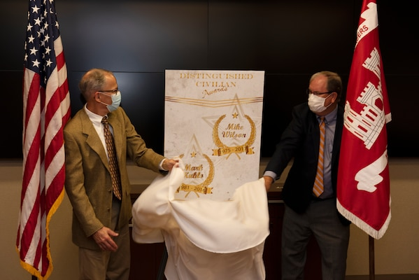 Mike Wilson (Right) and Mark Kuhlo, 2021 Distinguished Civilian Employee Recognition Award recipients, unveil a poster signifying the accolade during an award ceremony Oct. 6, 2021 at the Nashville District Headquarters in Nashville, Tennessee. Wilson retired in 2017 following 42 years of federal service, culminating his career as deputy district engineer for Project Management. Kuhlo retired in 2016 following 35 years of federal service, culminating his career as chief of the Electrical and Mechanical Branch. (USACE Photo by Lee Roberts)