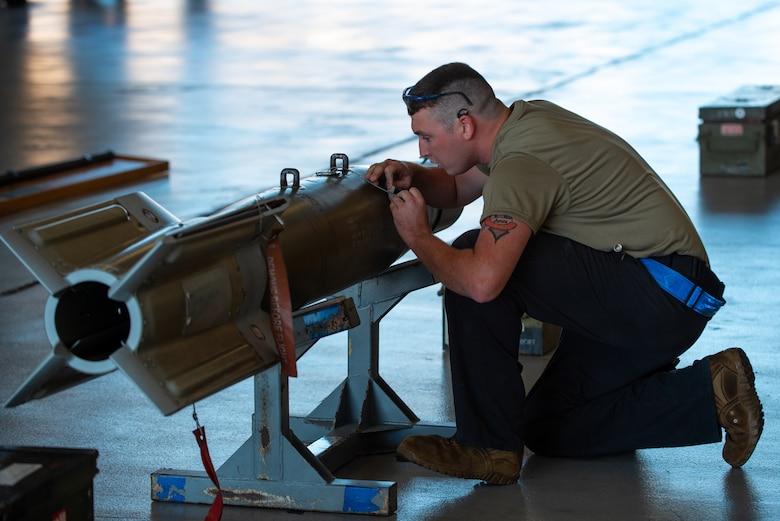 man kneeling next to a missile