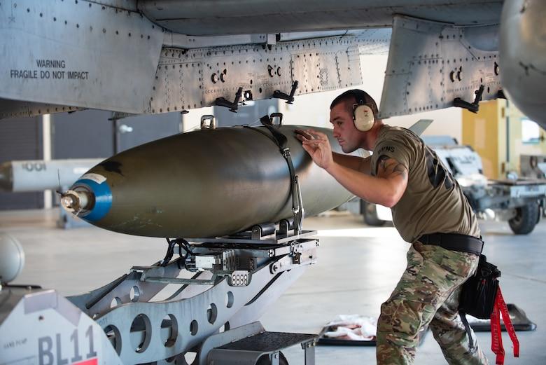 man loading missile on a plane