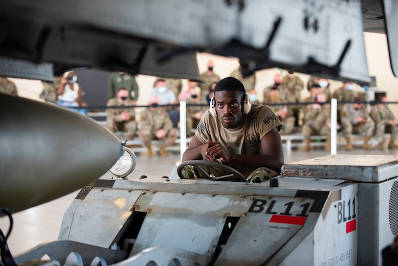 man loading a missile on a jet