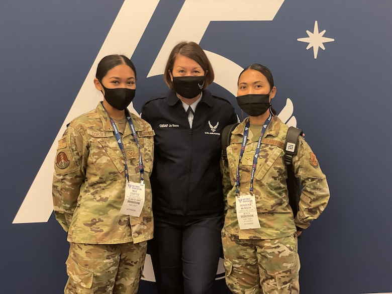 """Senior Airman Mae Cortez (left), a Physical Therapy Technician with the 90th Operational Medical Readiness Squadron, Chief Master Sergeant of the Air Force JoAnne S. Bass (center), and Airman 1st Class Rendora Munson, a Financial Operations Technician with the 90th Comptroller Squadron, pose for a picture at the Air Force Association's 2021 Air, Space and Cyber Conference. The conference featured many speakers who spoke on the theme of this years conference; """"air and space leadership for our nation: today and tomorrow."""""""