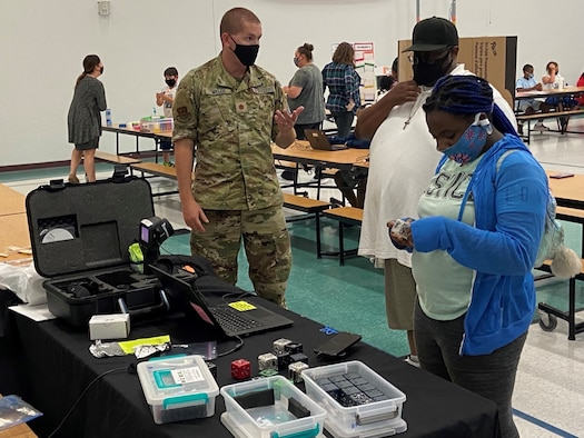Maj. Daniel Miller, an Air Force Institute of Technology student, explains how the new Air Force Research Laboratory cubelet's work to a student and her parent during North Dayton School of Discovery's first STEM night Sept. 16. (Contributed photo)