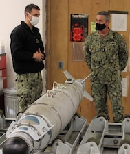 (Oct. 6, 2021) WHIDBEY ISLAND, Wash. -- Aviation Ordnanceman First Class Scott Olmstead explains the GBU-54 v2 Laser Joint Direct Attack Munition to Rear Adm. Pete Garvin, commander, Naval Education and Training Command, in the aviation ordnance bomb build-up lab at the Center for Naval Aviation Technical Training Unit Whidbey Island. (U.S. Navy photo)