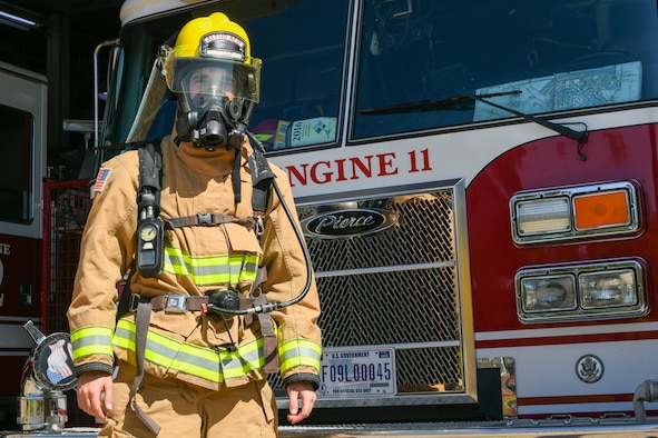 U.S. Air Force Airman 1st Class Joseph Coveney, 97th Civil Engineer Squadron (CES) fire prevention specialist, dons full gear in front of Engine 11 at the fire department on Altus Air Force Base, Oklahoma, Oct. 4, 2021. Coveney hails from a family of military and firefighters, who inspired him to enlist and be a firefighter himself. (U.S. Air Force photo by Airman 1st Class Trenton Jancze)