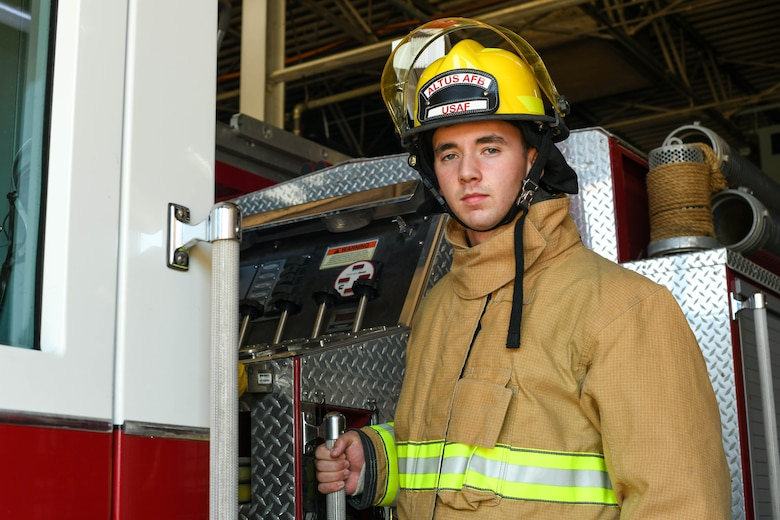 U.S. Air Force Airman 1st Class Joseph Coveney, 97th Civil Engineer Squadron (CES) fire prevention specialist, poses on Engine 11 at the fire department on Altus Air Force Base, Oklahoma, Oct. 4, 2021. The 97th CES Fire and Emergency Services Flight has more than 70 full time and part time staff. (U.S. Air Force photo by Airman 1st Class Trenton Jancze)