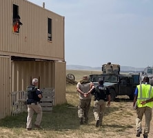 """Office of Special Investigations Nuclear Convoy Support Agents from Field Investigations Region 8, arrest a hostile """"terrorist"""" and lead him to the FBI, while a photographer documents the scenario during the Air Force Global Strike Command's Road Warrior Exercise at Camp Guernsey, Wyo., Aug. 9-20, 2021. (Photo by Col. Seth Miller, 8 FIR/CC)"""