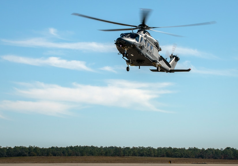 A helicopter hovers above an airfield.