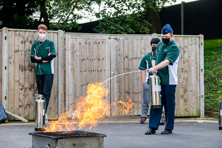 A student from the Alconbury Middle Highschool extinguishes a fire during safety training at RAF Alconbury, England, Oct. 4,2021. The training was a part of Fire Prevention Week which allowed firefighters from the 423rd CES to educate Airmen and family members from the 501st Combat Support Wing on proper fire safety habits. (U.S. Air Force photo by Senior Airman Eugene Oliver)