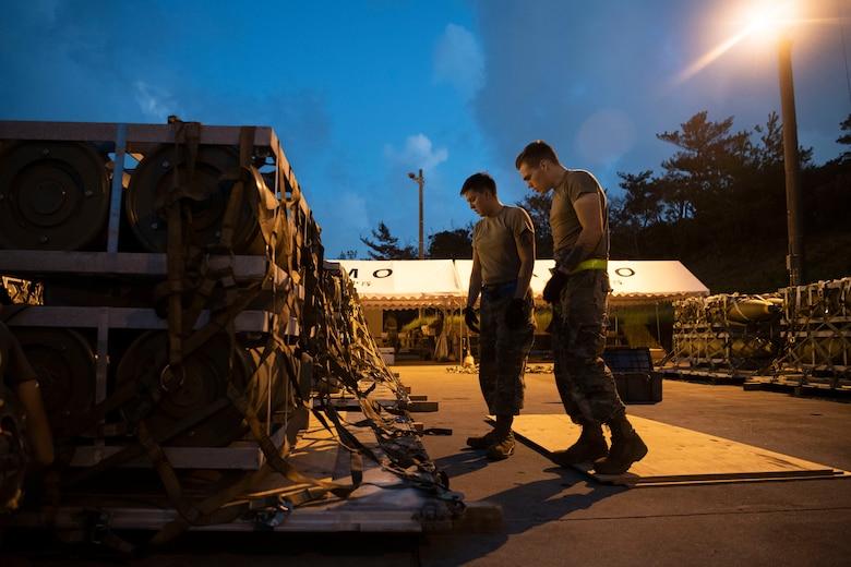 Two 18th MUNS Airmen build pallets.