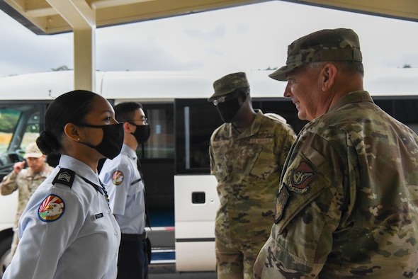 Two military members in uniform stand outside a school and talk to students in JROTC uniforms.