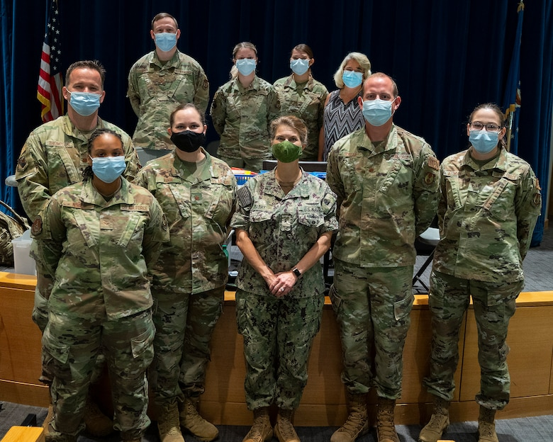 Rear Adm. Kristen Fabry (center), Defense Logistics Agency Land and Maritime commander, poses Oct. 1, 2021, with a group of 88th Medical Group Airmen during a visit to the Medical Center at Wright-Patterson Air Force Base, Ohio. The Airmen were part of a team that traveled to Columbus earlier this year to administer COVID-19 vaccines to DLA members in Fabry's command, and she wanted to personally thank them. (U.S. Air Force photo by R.J. Oriez)