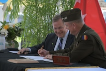 Two men sitting at table signing documents.