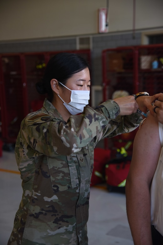 U.S. Air Force Senior Airman Angelina Lee, 17th Healthcare Operations Squadron aerospace allergy and immunization tech, administers a flu shot to a member