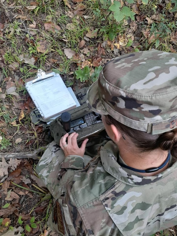 A woman in camouflage with her back to the camera kneels while holding a radio in front of her.