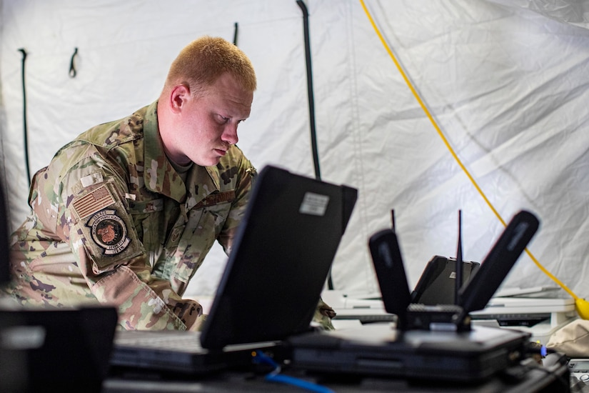 A soldier works on a laptop.